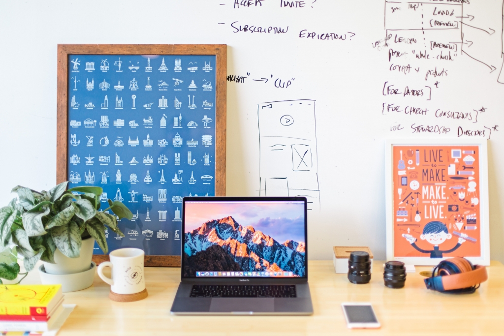 Desk with computer, frames and whiteboard with scribbles Digital Marketing
